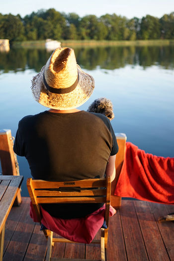 Rear view of man sitting on chair at lake