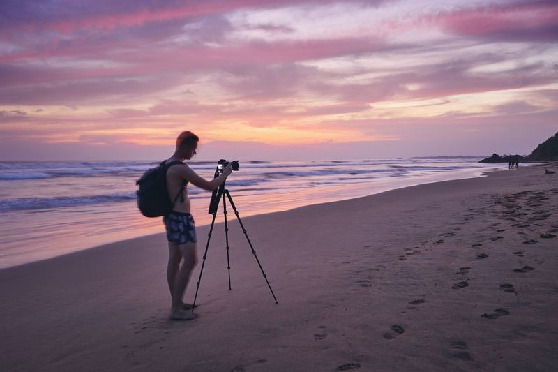 Young man photographing with tripod at beach after sunset. Photographer in blurred motion. Skill  Inspiration Creativity Full Length Moody Sky Travel Hobby Occupation Digital Camera Scenics - Nature Backpack Photographic Equipment Beauty In Nature Camera - Photographic Equipment Photography Themes Long Exposure Tripod Beach Sea Sunset Photographing Photographer Photography Man Real People