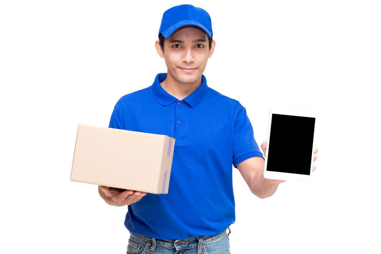 Portrait of salesman holding cardboard box and digital tablet while standing against white background