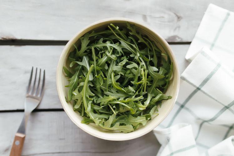 Green fresh arugula salad leaves in bowl, fork on white wooden background, white towel