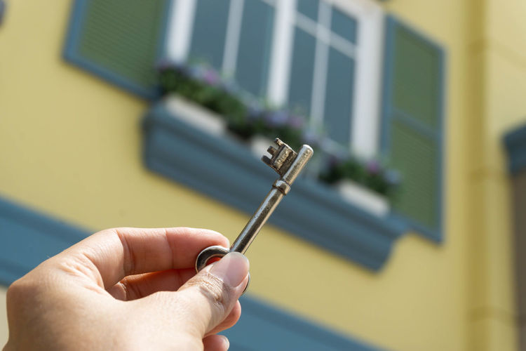 Close-up of hand holding key against blurred building