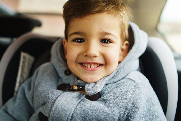 Portrait of cute boy sitting in car