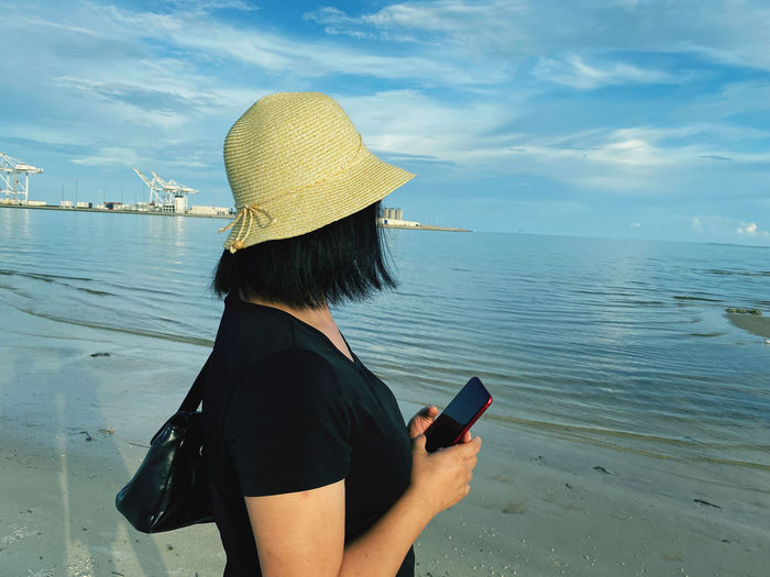 Rear view of woman using mobile phone in sea