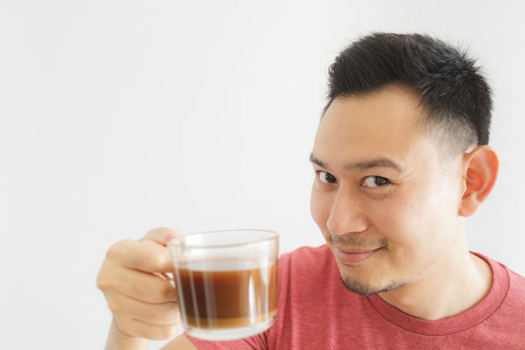 Portrait of young man drinking glass against white background