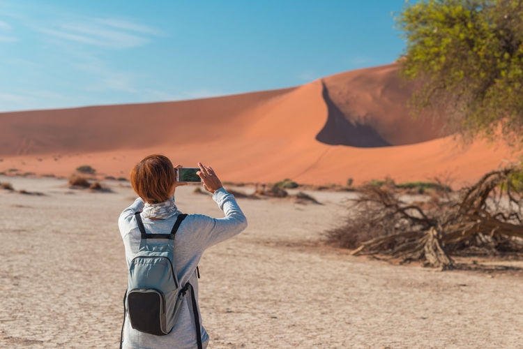 Rear view of woman photographing desert through mobile phone