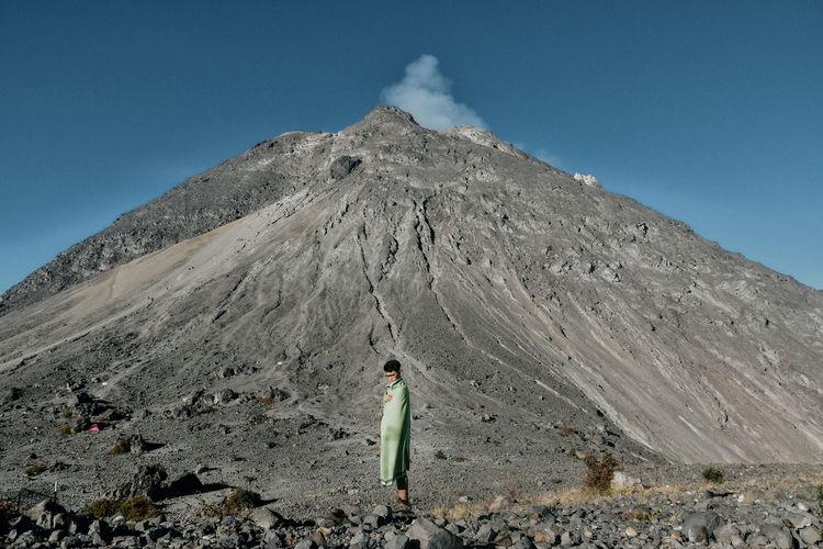 Full length of boy standing against volcano