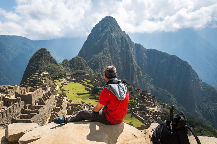 Rear view of man sitting on mountain against machu picchu