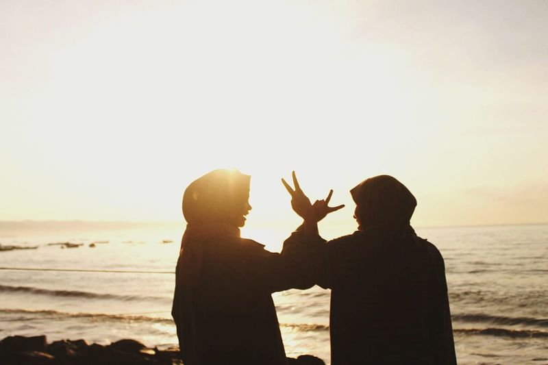Silhouette friends gesturing peace sign while standing on beach against clear sky during sunset