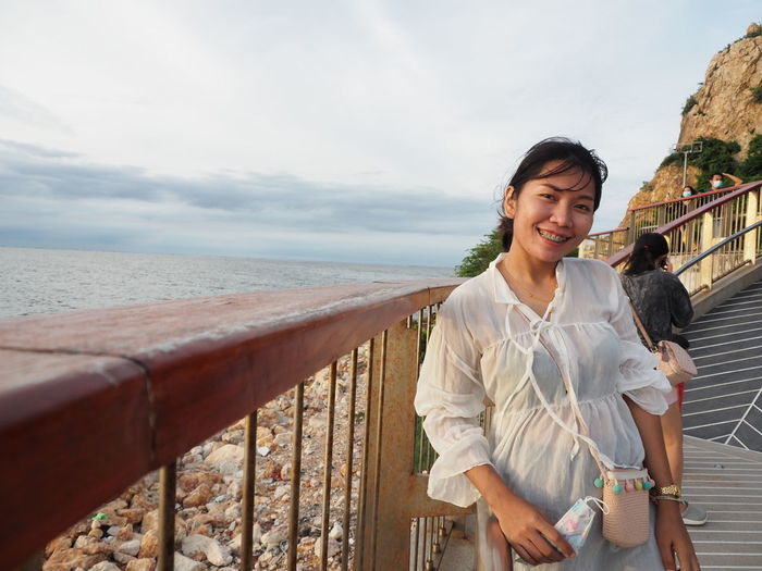 Smiling young woman standing by railing against sea
