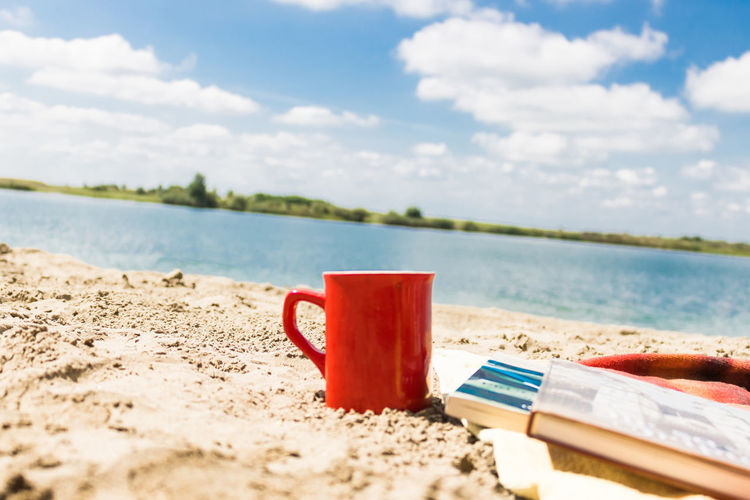 Water Beach Sea Sky Cloud - Sky Sand Day Nature Tranquility Scenics - Nature No People Food And Drink Red Tranquil Scene Outdoors Cup Mug Sandy Beach Summer Summertime Vacations Copy Space Serenity Relaxation Coffee - Drink Coffee Cup Drink Refreshment Book Literature Novel