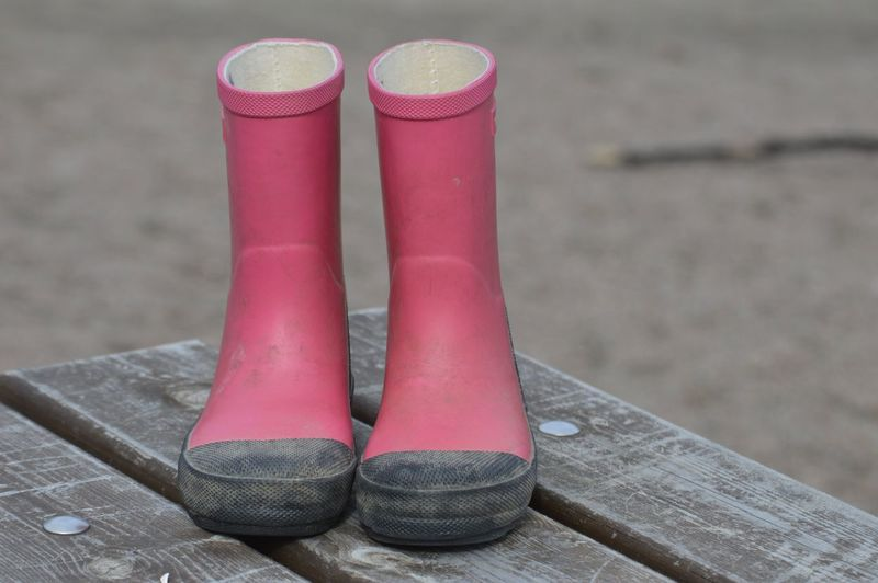 Close-up of rubber boots on table outdoors