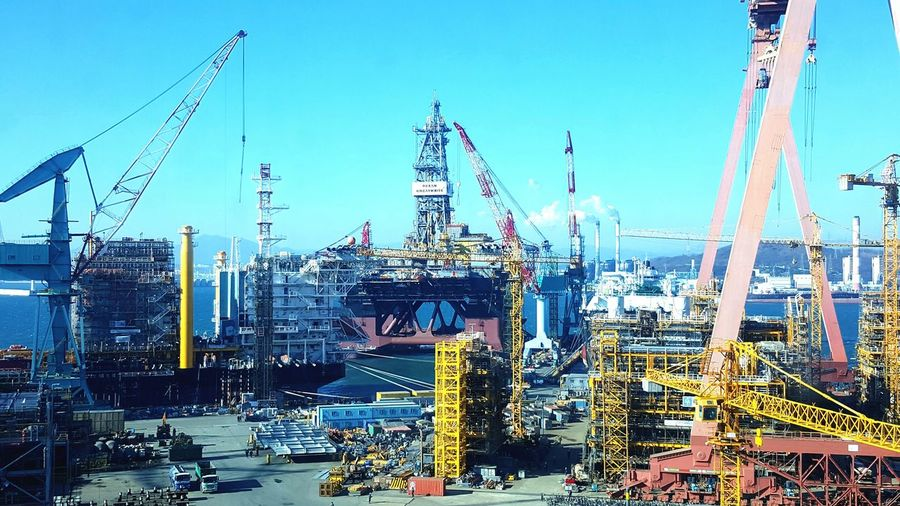 Cranes at commercial dock with oil rig against sky