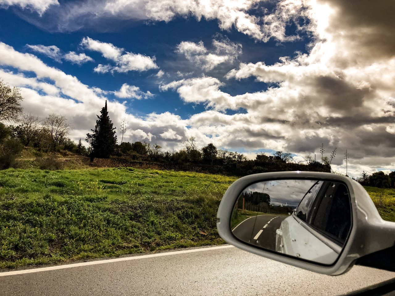 cloud - sky, sky, side-view mirror, transportation, car, road, day, land vehicle, grass, tree, nature, no people, vehicle mirror, mode of transport, outdoors, landscape, growth, beauty in nature