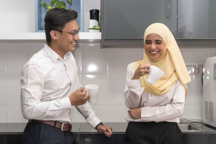 Two young executive malay having a break at pantry Young Adult Smiling Front View Young Women Two People Standing Adult Real People Holding Young Men Happiness Cup Lifestyles Coffee - Drink Three Quarter Length Men Mug Togetherness Coffee Cup