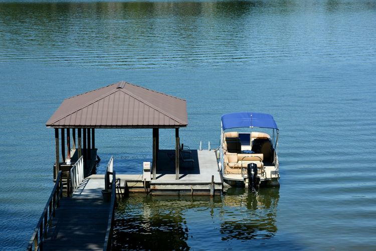 high angle view of pontoon boat along side dock in lake