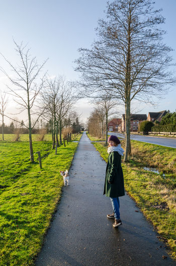 Rear View Of Women Walking With Dog On Footpath With Bare Trees During Winter