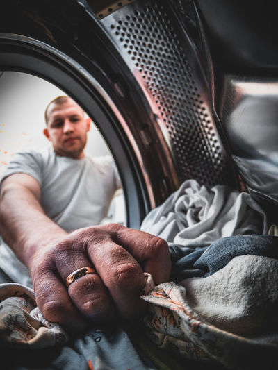 Low angle view of man putting garments in washing machine