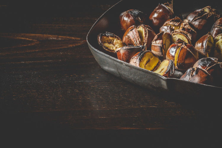 Roasted chestnuts in iron grilling pan over rustic wooden table with copy space. Autumn Chestnut Chestnuts Cooking Iron Meal Snack Brown Food Fried Fruit Gourmet Healthy Heap Ingredient Nut Opened Pan Roasted Roasting Seasonal Sweet Tasty Traditional Wooden