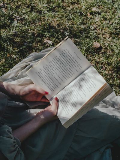 High angle view of man reading book on field