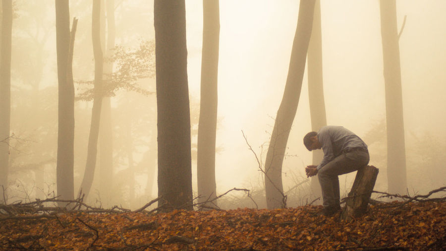 Side view of depressed man sitting on tree stump in foggy forest