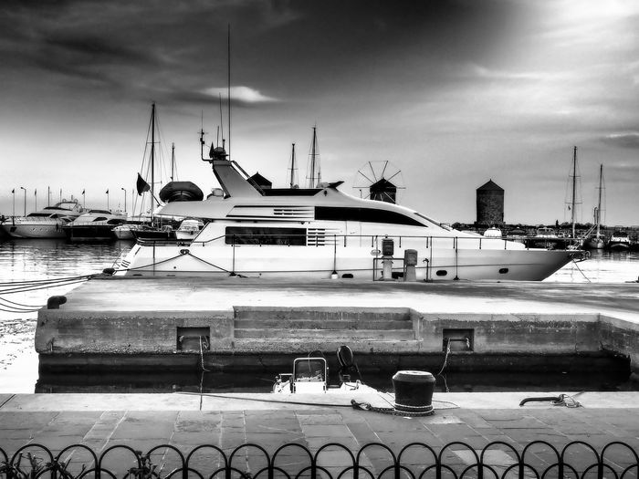 Yacht moored at harbor against cloudy sky