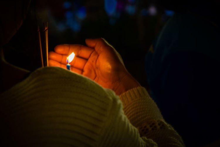 Close-up of hand holding lit candle at night