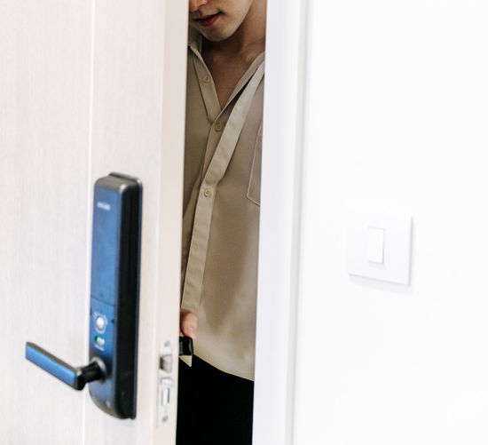 Midsection of man holding door