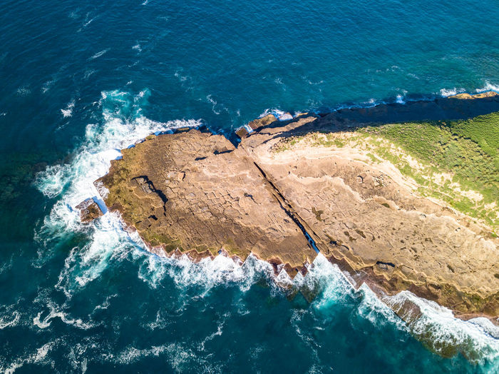 Aerial view of rocks by sea