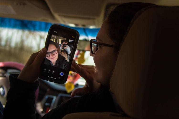 Woman taking selfie with friend in car