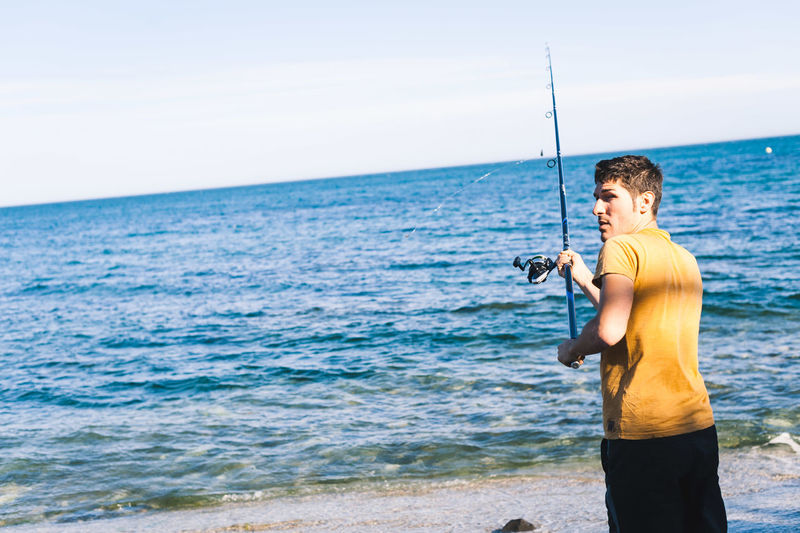 Young man fishing on beach