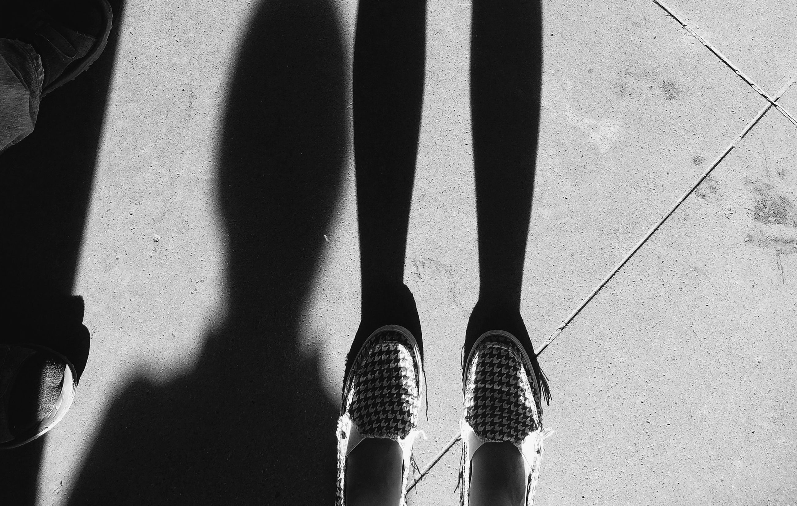 low section, shoe, person, part of, shadow, street, standing, metal, high angle view, unrecognizable person, close-up, men, day, personal perspective, transportation, outdoors, footwear