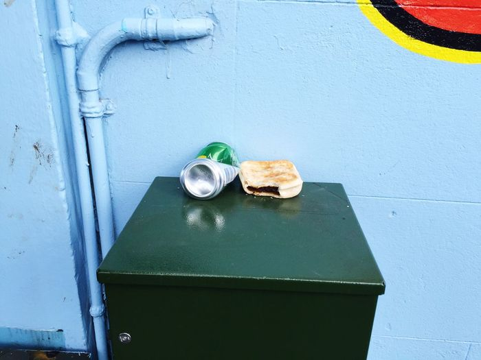 Abandoned drink can by bread on table against wall