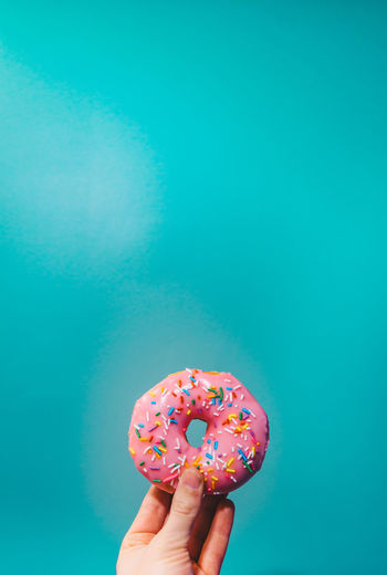 Pink donut against turquoise background Food And Drink Freshness Background Close-up Cupcake Day Dessert Donut Food Food And Drink Fresh Freshness Holding Human Body Part Human Hand Indulgence Lifestyles Multi Colored One Person People Pink Color Ready-to-eat Real People Sprinkles Studio Shot Sweet Food Tasty Temptation Turquoise Unhealthy Eating Unrecognizable Person