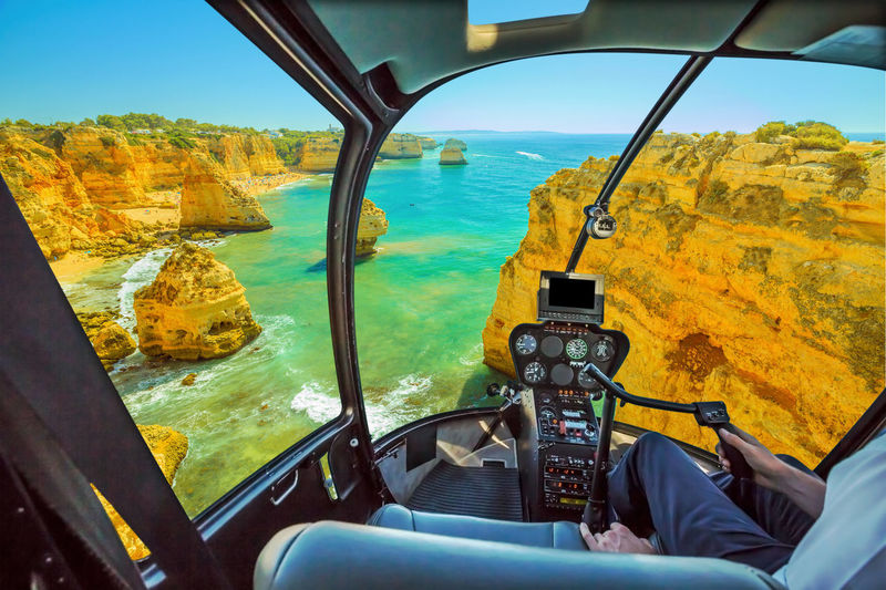 Helicopter cockpit interior flying on scenic landscape of boat trip between cliffs and natural rock formations of Ponta da Piedade. Scenic flight above Lagos, Algarve, Portugal skyline, Atlantic Ocean Cockpit View Cockpit Interior Flight Scenic Flight Flying Aerial View Panorama Skyline Beach Sea Seascape Portugal Rock Formation Douro River Portugal Serra Do Pilar Vila Nova De Gaia Oporto City Sunset Window Azenhas Do Mar Ponta Da Piedade Marinha Beach Natural Arch Helicopter Transportation Water Mode Of Transportation Nature Vehicle Interior Day Transparent Glass - Material Outdoors Air Vehicle Airplane Windshield No People Sky