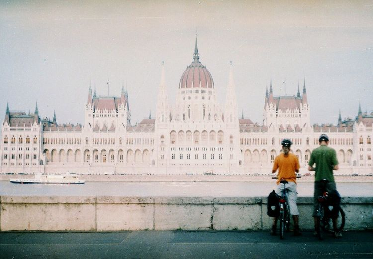 Rear view of people standing with bicycle against hungarian parliament building