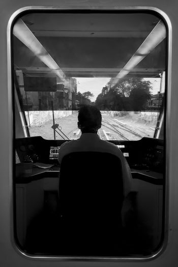 Rear View Transparent Window Mode Of Transportation Transportation Glass - Material Real People One Person Men Vehicle Interior Public Transportation Lifestyles Travel Day Land Vehicle Sitting Indoors  Journey Train Driver Rails Blackandwhite Light And Shadow