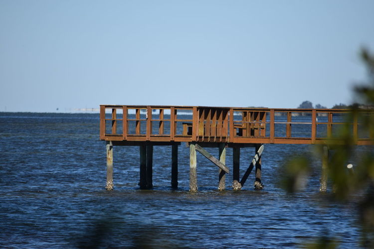 Scenic view of jetty with calm sea against blue sky