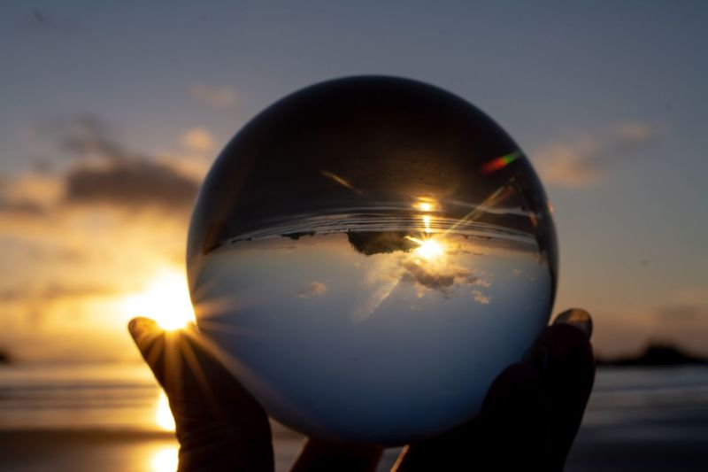 Cropped hand of woman holding crystal ball at beach against sky during sunset