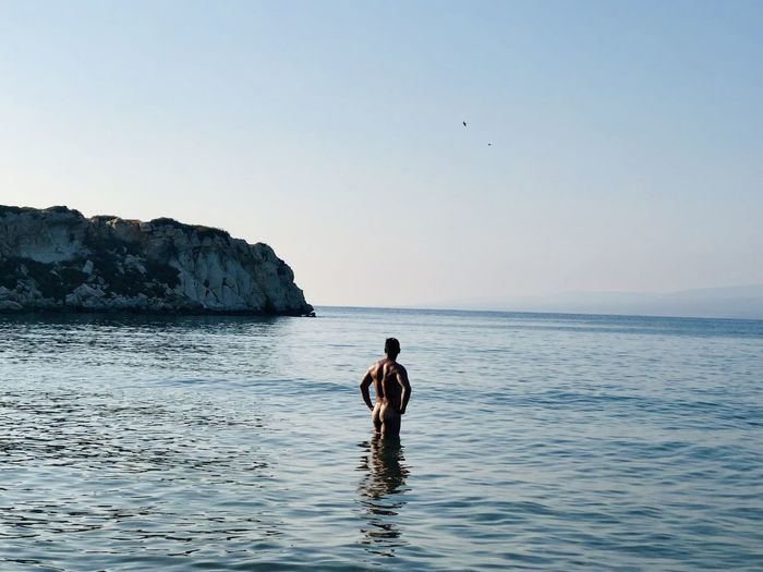 Rear view of naked man standing in sea