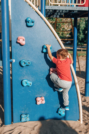 Rear view of boy on slide at playground