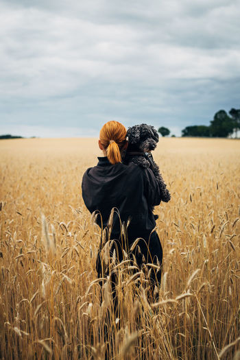 Rear view of woman with dog standing in farm
