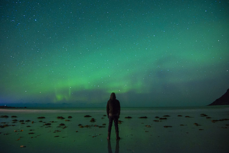 Rear view of man standing by sea against aurora borealis in sky at night
