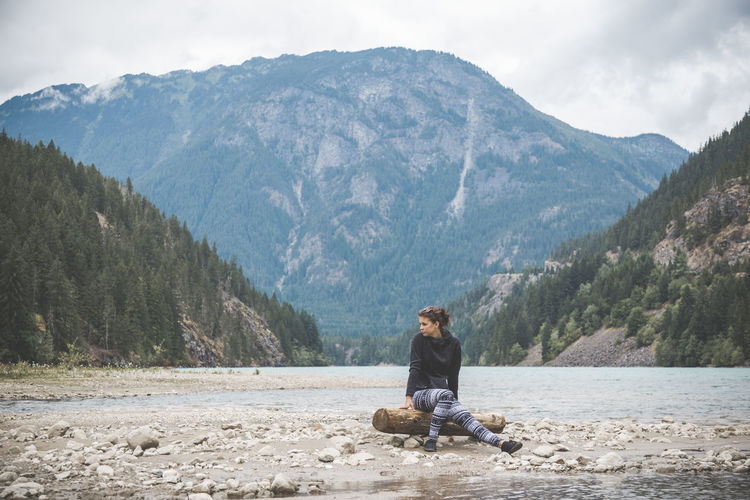 Woman sitting on log by lake against mountain