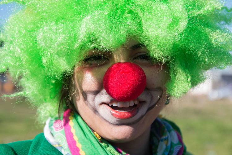 Close-up portrait of smiling woman in clown costume