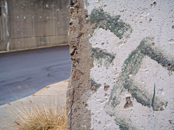 Close-up of damaged wall by road