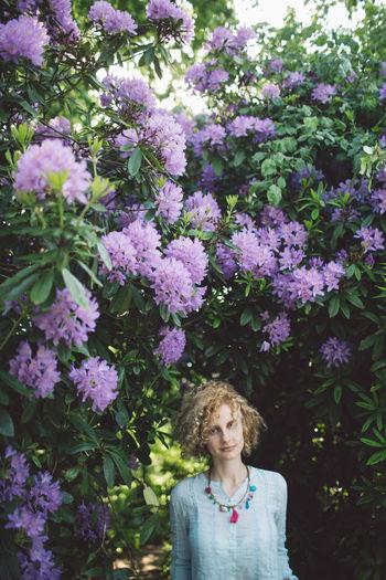 Portrait Of Woman Against Purple Flowering Plants