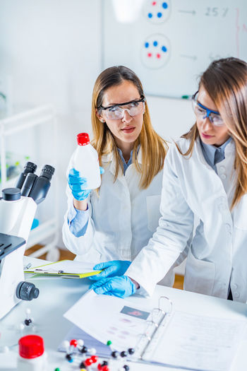 Female scientists examining chemical in laboratory