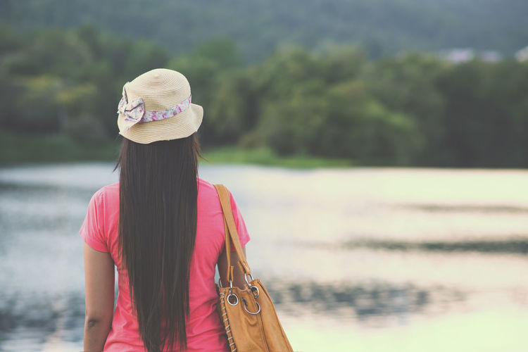 Traveler Asian woman still looking at the beautiful of landscape happily. vintage color effect Holiday Relaxing Travel Woman Day Lake Leisure Activity Lifestyles Nature One Person Outdoors People Rear View Scenics Sky Standing Vacation Water Women Young Women