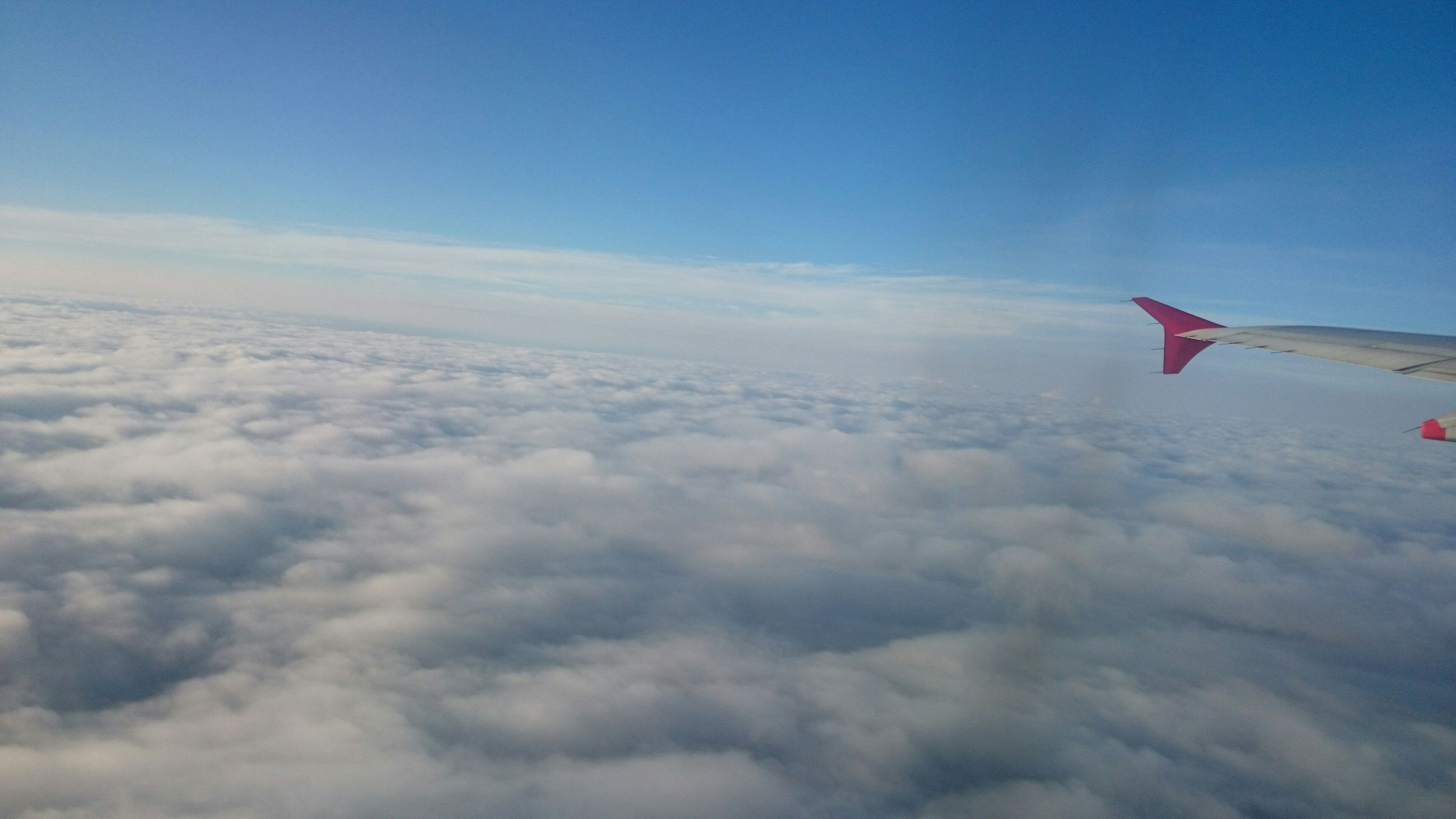 sky, flying, airplane, cloud - sky, blue, air vehicle, beauty in nature, aircraft wing, scenics, nature, cloudscape, transportation, cloud, white color, tranquility, tranquil scene, mid-air, part of, outdoors, day