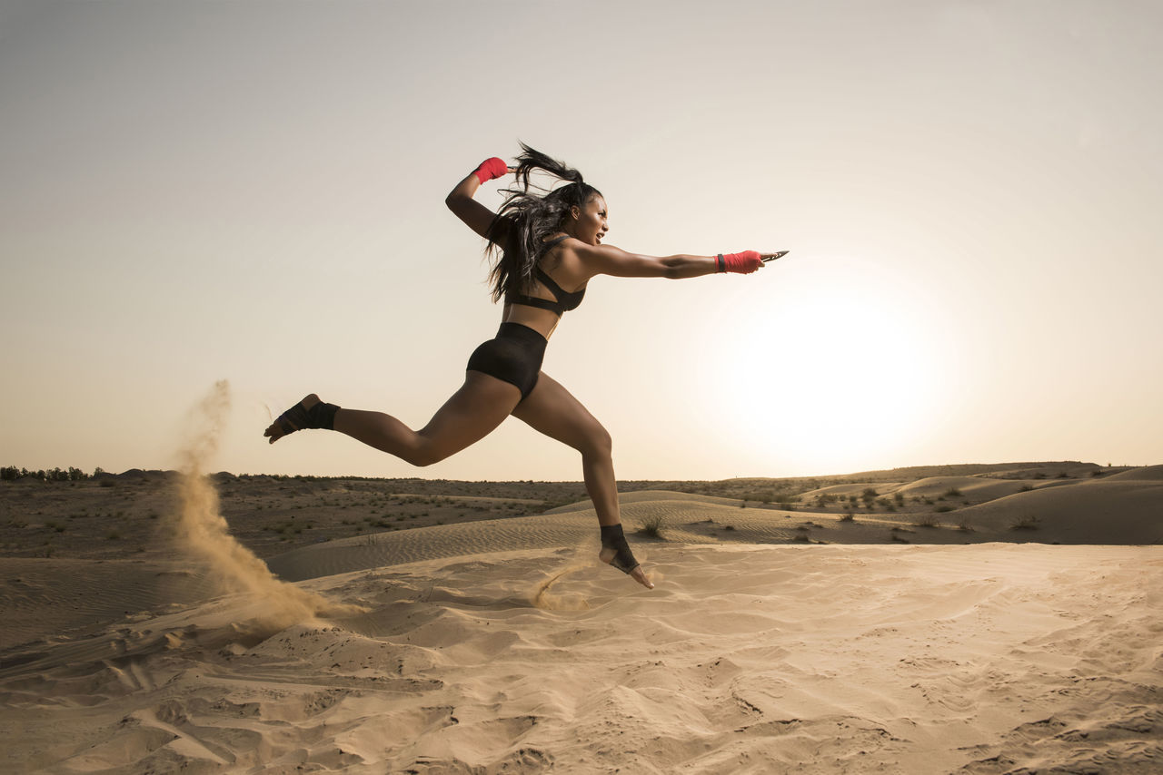 Woman Jumping On Desert Against Clear Sky